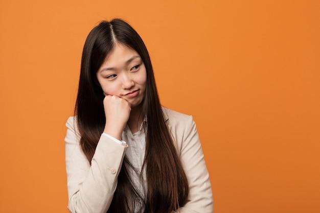 Mulher chinesa do negócio novo que sente triste e pensativa, olhando o espaço da cópia.