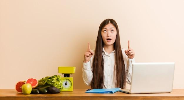 Mulher chinesa do nutricionista novo que trabalha com seu laptop que aponta de cabeça com a boca aberta.