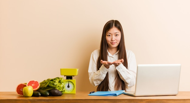 Mulher chinesa do nutricionista novo que trabalha com seu portátil que guarda algo com palmas