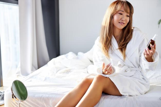 Mulher chinesa em roupão de banho lê indicações de uso e composição de cosméticos na garrafa, procedimentos de beleza em casa em quarto bem iluminado