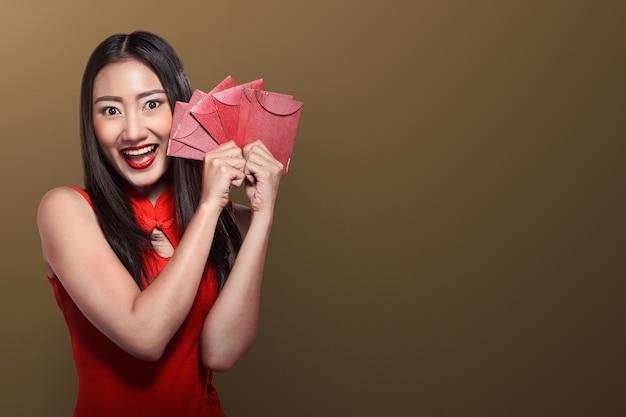 Mulher chinesa, em, tradional, roupa, segurando, angpao