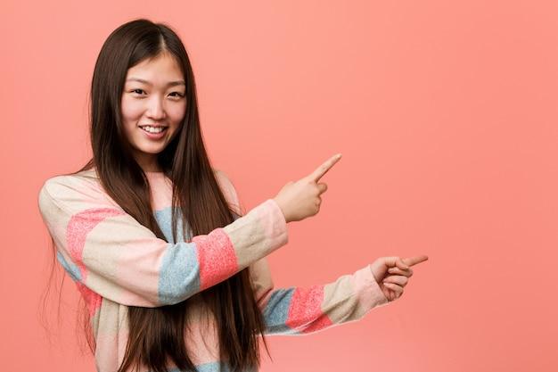 Mulher chinesa fresca nova excitada apontando com dedo indicador longe.