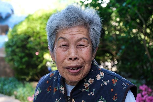 Mulher chinesa idosa posando em um parque público.