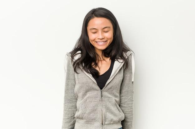 Mulher chinesa jovem aptidão ri e fecha os olhos, sente-se relaxado e feliz.