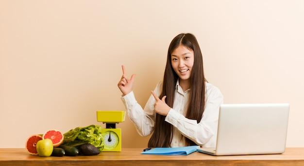 Mulher chinesa jovem nutricionista trabalhando com seu laptop apontando com o dedo indicador para um espaço de cópia, expressando emoção e desejo.