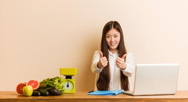 Mulher chinesa jovem nutricionista trabalhando com seu laptop com polegares para cima, um brinde por algo