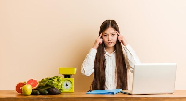 Mulher chinesa jovem nutricionista trabalhando com seu laptop focado em uma tarefa