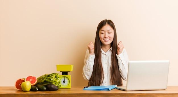 Mulher chinesa jovem nutricionista trabalhando com seu laptop, levantando o punho, sentindo-se feliz e bem sucedida.