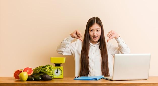 Mulher chinesa jovem nutricionista trabalhando com seu laptop, mostrando o polegar para baixo e expressando antipatia.