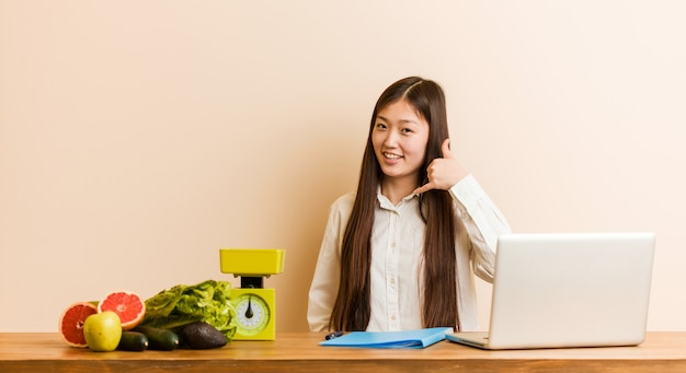 Mulher chinesa jovem nutricionista trabalhando com seu laptop, mostrando um gesto de chamada de telefone móvel com os dedos.