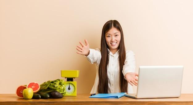Mulher chinesa jovem nutricionista trabalhando com seu laptop se sente confiante dando um abraço