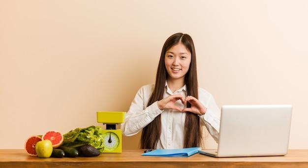 Mulher chinesa jovem nutricionista trabalhando com seu laptop, sorrindo e mostrando uma forma de coração com as mãos.