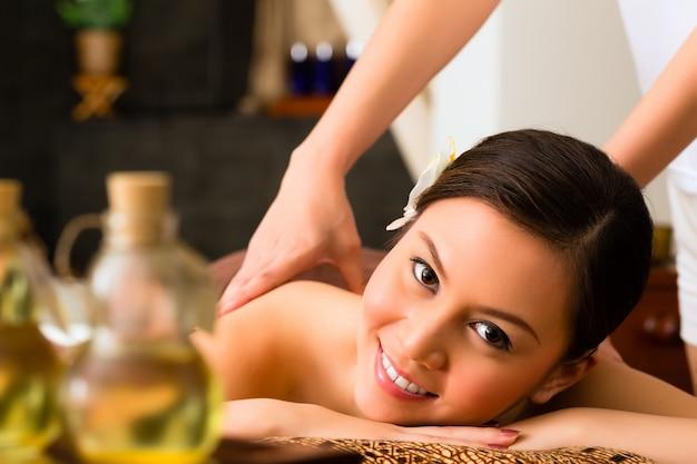 Mulher chinesa na massagem de bem-estar com óleos essenciais