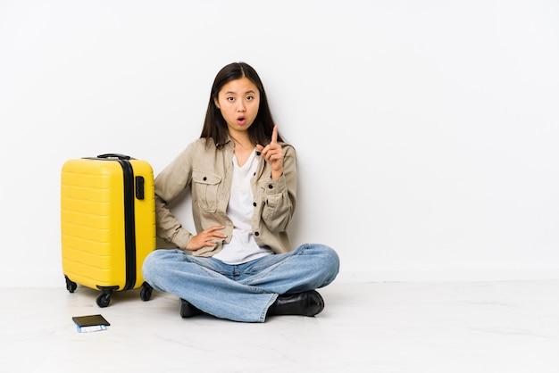 Mulher chinesa nova do viajante que senta guardando um cartão de embarque que tem uma ideia, conceito da inspiração.