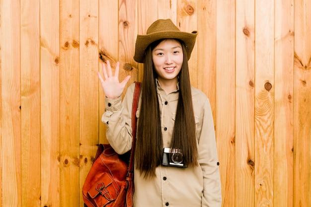 Mulher chinesa nova do viajante que sorri mostrando alegre número cinco com dedos.