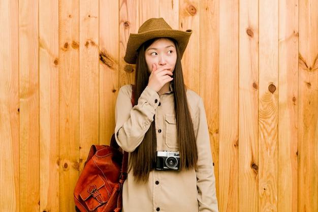 Mulher chinesa nova do viajante vista pensativa a um espaço da cópia que cobre a boca com a mão.