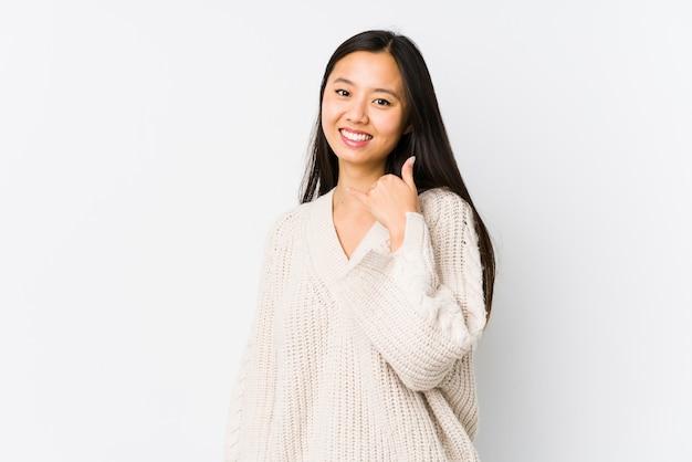 Mulher chinesa nova isolada mostrando um gesto de chamada de telefone móvel com dedos.
