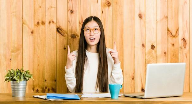 Mulher chinesa nova que estuda em sua mesa que aponta de cabeça com boca aberta.