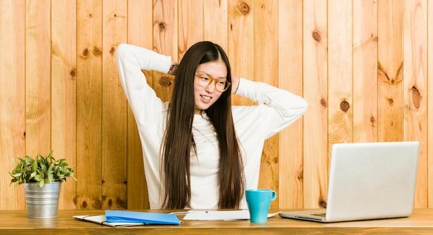 Mulher chinesa nova que estuda em sua mesa que estica os braços, posição relaxado.