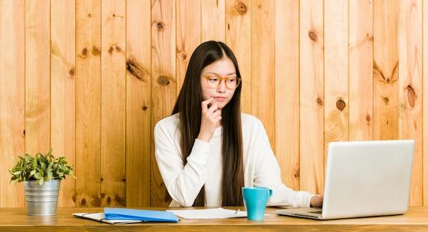 Mulher chinesa nova que estuda em sua mesa que olha lateralmente com expressão duvidosa e cética.