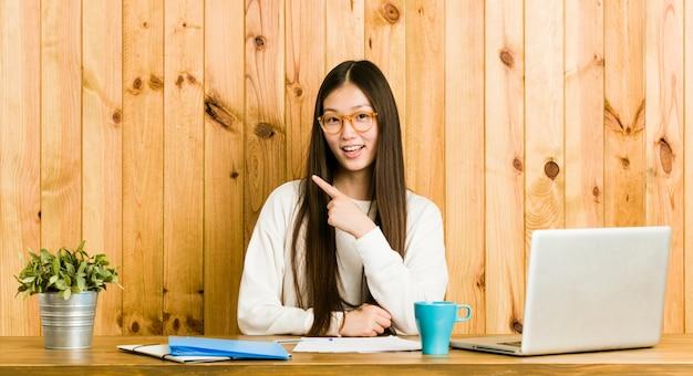 Mulher chinesa nova que estuda em sua mesa que sorri e que aponta de lado, mostrando algo no espaço em branco.