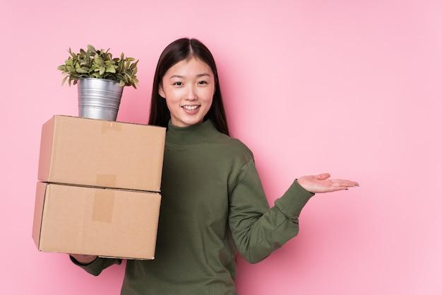 Mulher chinesa nova que mantém caixas isoladas mostrando um espaço da cópia em uma palma e segurando uma outra mão na cintura.