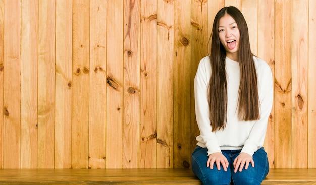 Mulher chinesa nova que senta-se em um lugar de madeira engraçado e amigável saindo da língua.