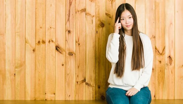 Mulher chinesa nova que senta-se em um lugar de madeira que aponta o templo com o dedo, pensando, focalizado em uma tarefa.