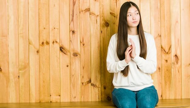 Mulher chinesa nova que senta-se em um lugar de madeira que compõe o plano na mente, configurando uma ideia.