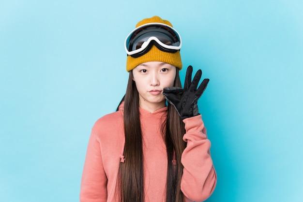 Mulher chinesa nova que veste a roupa do esqui isolada com os dedos nos bordos que mantêm um segredo.