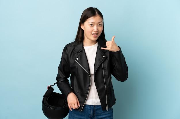 Mulher chinesa segurando um capacete de motociclista sobre um azul isolado fazendo gesto de telefone