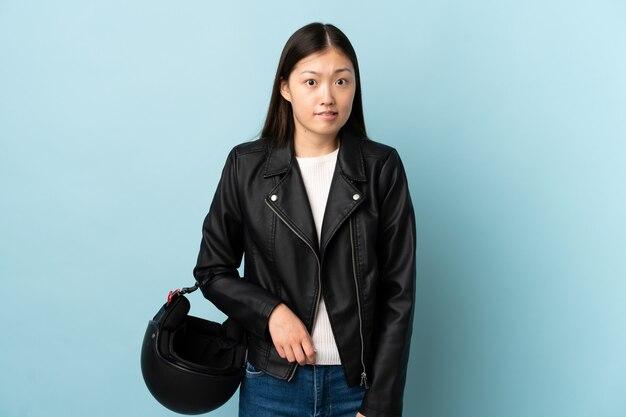Mulher chinesa segurando um capacete de motociclista sobre uma parede azul isolada, com dúvidas e expressão facial confusa