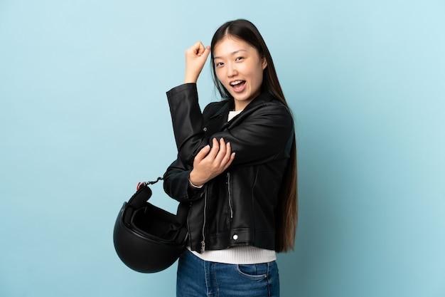 Mulher chinesa segurando um capacete de motociclista sobre uma parede azul isolada, fazendo um gesto forte