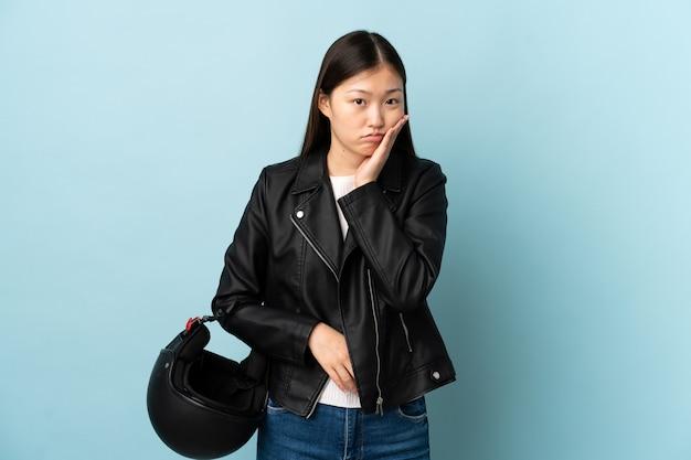 Mulher chinesa segurando um capacete de motociclista sobre uma parede azul isolada, infeliz e frustrada