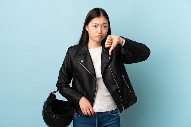 Mulher chinesa segurando um capacete de motociclista sobre uma parede azul isolada, mostrando uma placa com o polegar para baixo