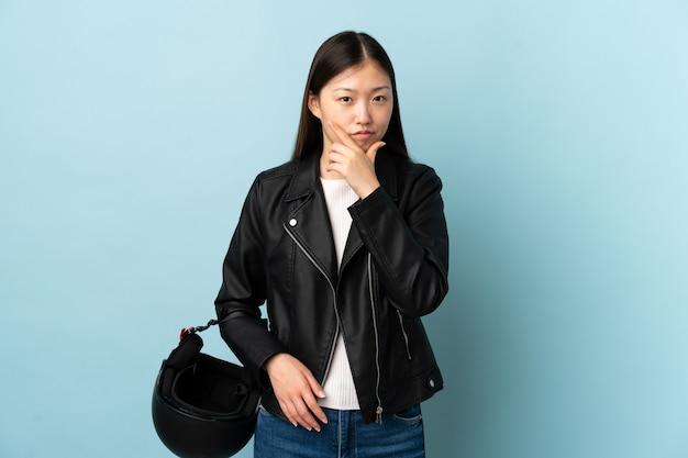 Mulher chinesa segurando um capacete de motociclista sobre uma parede azul isolada, pensando uma ideia