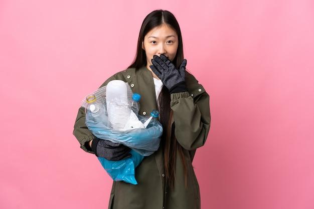 Mulher chinesa segurando uma sacola cheia de garrafas de plástico para reciclar na boca isolada rosa feliz e sorridente com a mão
