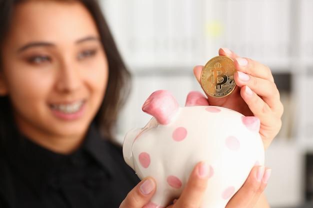 Mulher chinesa sorridente segurando a moeda dentro piggybank