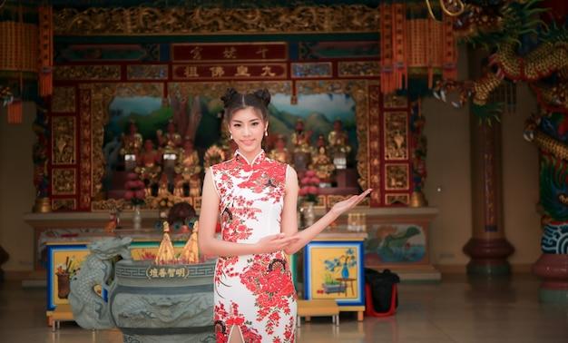 Mulher chinesa sorridente vestido de cheongsam tradicional no ano novo. templo chinês