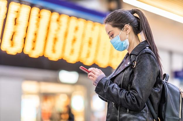 Mulher chinesa usando máscara facial na estação de trem