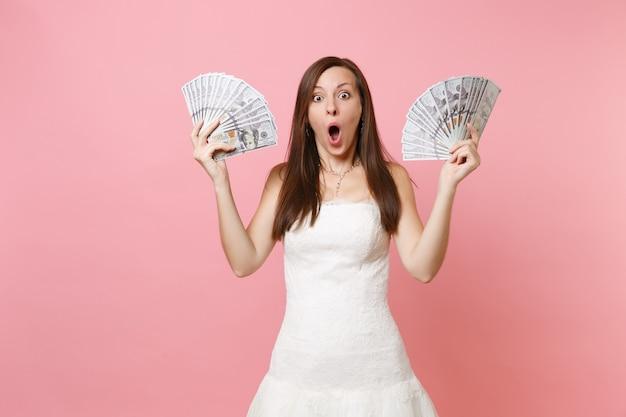 Mulher chocada com a boca aberta em um vestido branco segurando um pacote de muitos dólares, dinheiro vivo