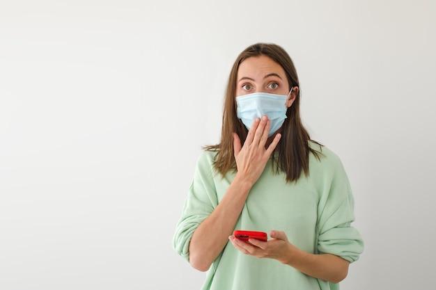 Mulher chocada com máscara usando smartphone