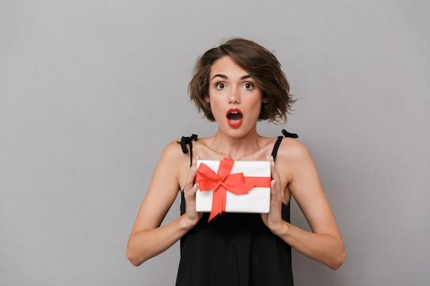 Mulher chocada com um vestido preto segurando uma caixa de presente, isolada sobre uma parede cinza