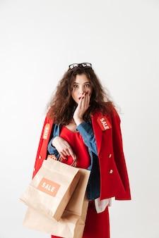 Mulher chocada compra venda espantada segurando sacolas de papel