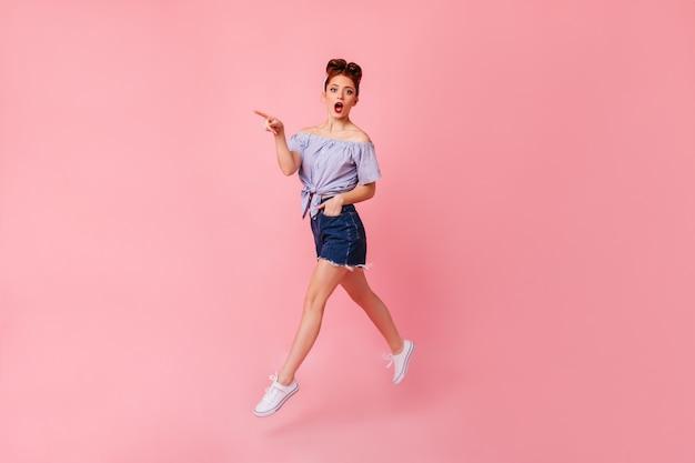 Mulher chocada de gengibre na blusa, apontando com o dedo. garota pin-up surpresa, pulando com a mão no bolso.