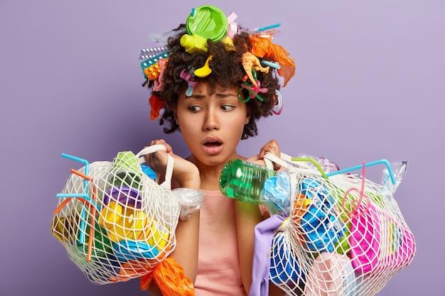 Mulher chocada de pele escura olha com olhos abertos e expressão preocupada, carrega dois sacos de rede com vários resíduos de plástico, envolvida em atividade de voluntariado, isolada na parede roxa