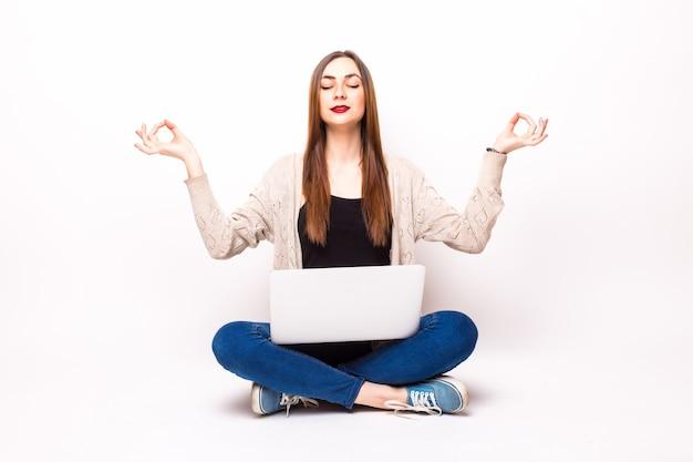 Mulher chocada e confusa em uma camiseta sentada no chão com um laptop, segurando óculos e olhando para a câmera sobre o cinza