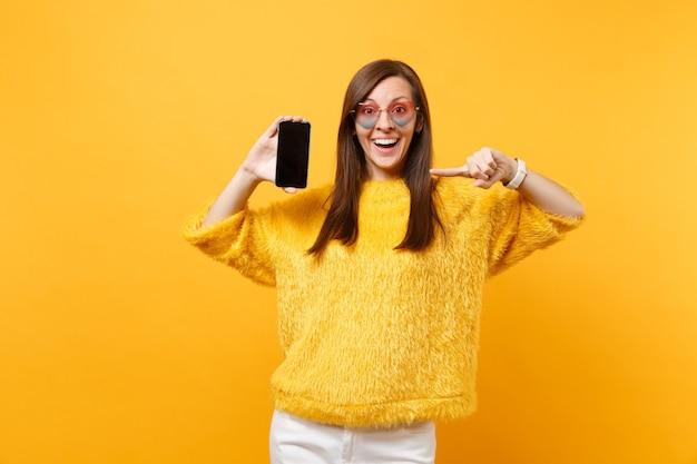 Mulher chocada e espantada em copos de coração apontando o dedo indicador no telefone móvel com tela vazia preta em branco isolada no fundo amarelo brilhante. pessoas sinceras emoções, estilo de vida. área de publicidade.
