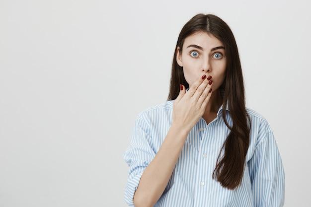 Mulher chocada e ofegante tapando a boca com a mão