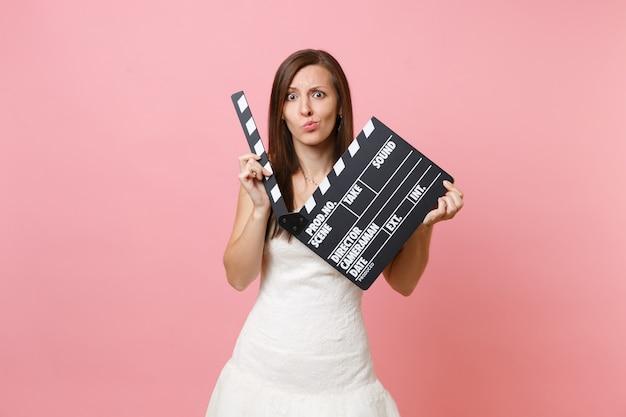 Mulher chocada e preocupada com um vestido branco segurando um clássico filme preto fazendo claquete